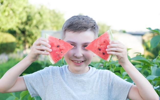 Criança feliz e sorridente comendo melancia no verão