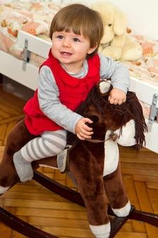 Criança feliz e um cavalo de balanço.