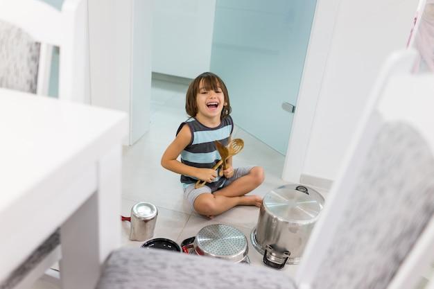 Criança feliz em casa brincando com pratos como instrumentos musicais e bateria