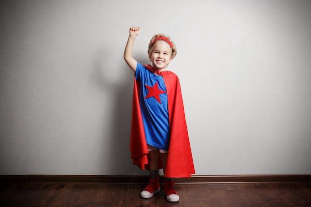 Criança feliz em roupa de super-herói contra parede cinza.