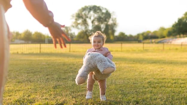 Criança feliz em roupas cor de rosa e ursinho de pelúcia