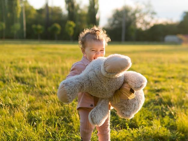 Criança feliz em roupas cor de rosa, segurando um ursinho de pelúcia