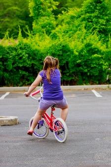 Criança feliz em uma bicicleta jovem garota andando de bicicleta em um dia ensolarado.