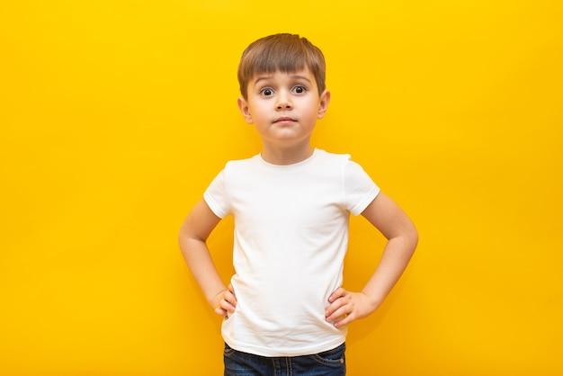 Criança feliz em uma camiseta branca com as mãos no cinto em uma parede amarela isolada
