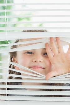 Criança feliz espreitando através de persianas