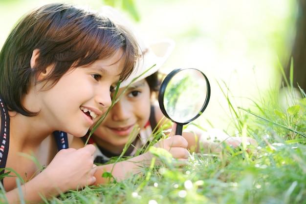 Criança feliz explorando a natureza com lupa