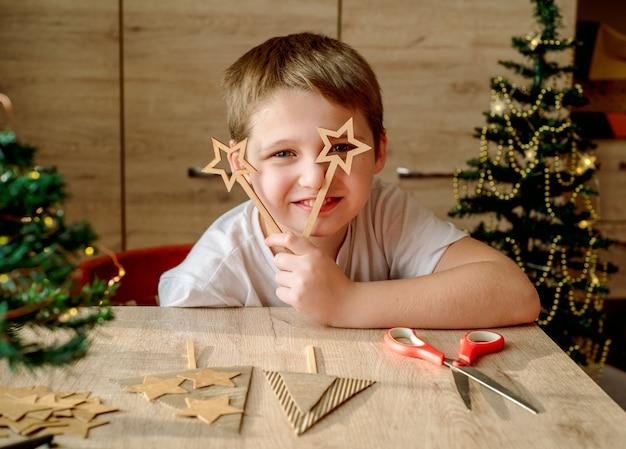 Criança feliz faz uma árvore de natal de papelão. sem desperdício, tendências ecológicas, desperdício zero.