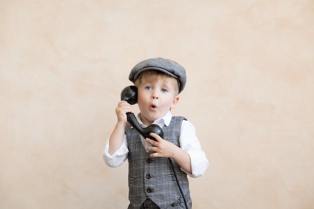Criança feliz finge ser empresários. garoto engraçado falando por telefone. conceito de negociações comerciais