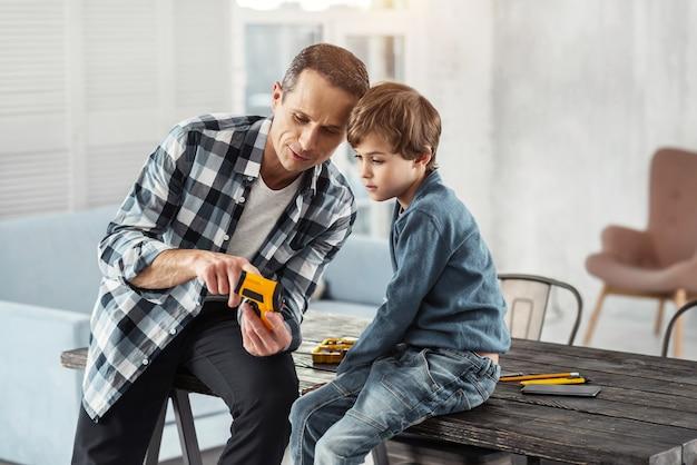 Criança feliz. homem bonito e alegre de cabelos escuros mostrando instrumentos para seu filho enquanto está sentado na mesa e seu filho sentado perto dele