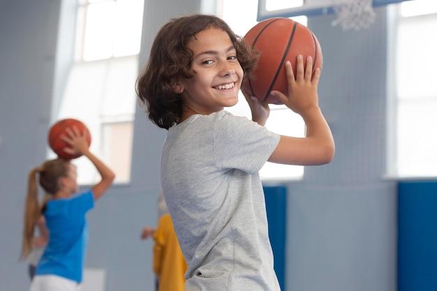 Criança feliz jogando basquete