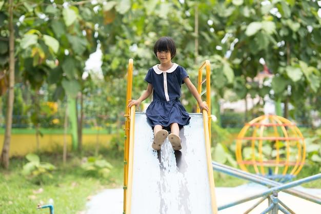 Criança feliz, jogando slider, em, pátio recreio