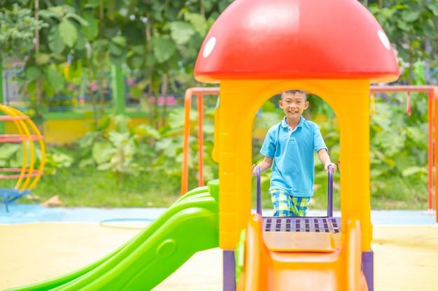Criança feliz jogando slider na zona de recreio