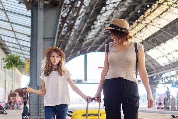 Criança feliz mãe e filha caminhando juntos na estação ferroviária com a mala de bagagem. viagem, turismo, transporte, conceito de família