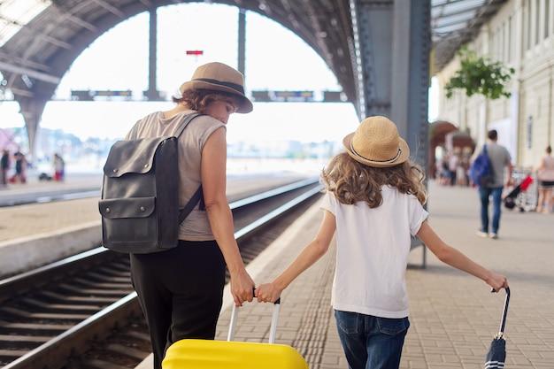 Criança feliz mãe e filha caminhando juntos na estação ferroviária com mala de bagagem, vista traseira. viagem, turismo, transporte, conceito de família