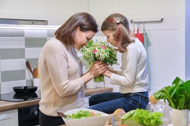 Criança feliz mãe e filha com buquê de primavera, presente de flores da menina para a mãe no dia das mães.