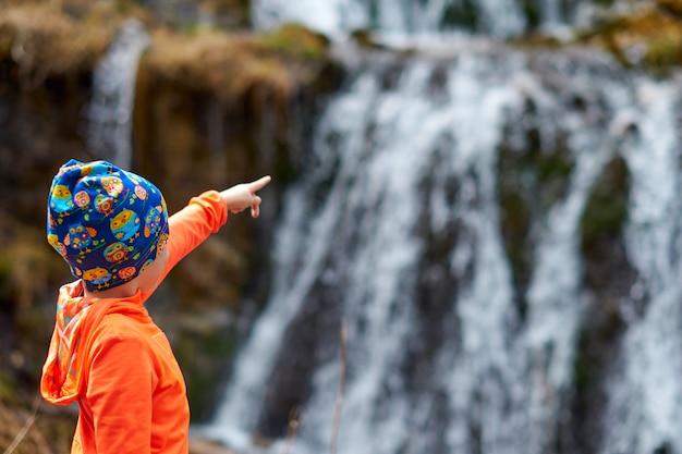 Criança feliz menina aponta o dedo na cachoeira. close-up retrato de esportes ao ar livre