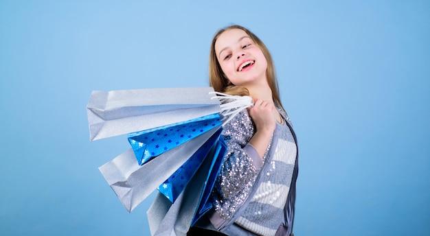 Criança feliz. menina com presentes. economia na compra de férias. compras para casa. moda infantil. assistente de loja com pacote. vendas e descontos. menina pequena com sacolas de compras. tempo incrível durante as compras.
