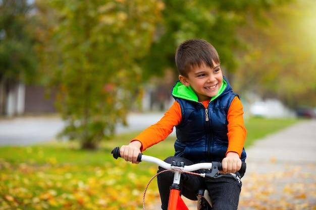 Criança feliz. menino de bicicleta em um parque da cidade. o conceito de relaxamento e diversão. foto com espaço vazio.