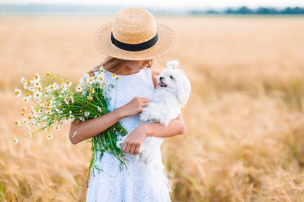 Criança feliz no campo de trigo. linda garota com um vestido branco e um chapéu de palha com trigo maduro nas mãos