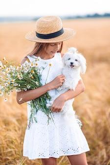 Criança feliz no campo de trigo. linda garota de vestido branco ao ar livre