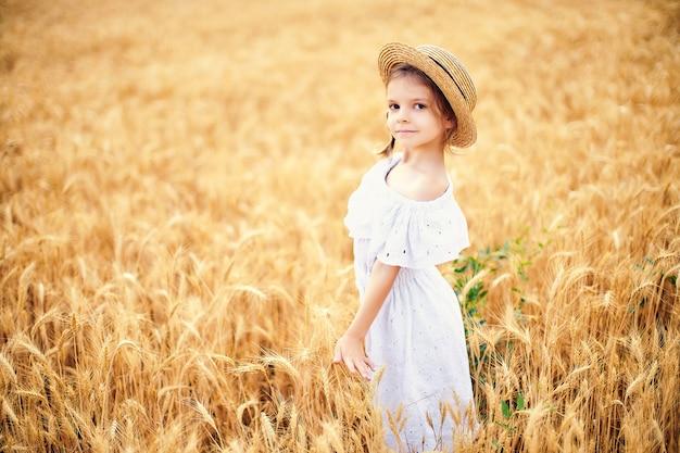 Criança feliz no campo de trigo outono. menina bonita no vestido branco e chapéu de palha divirta-se com a brincar, a colheita