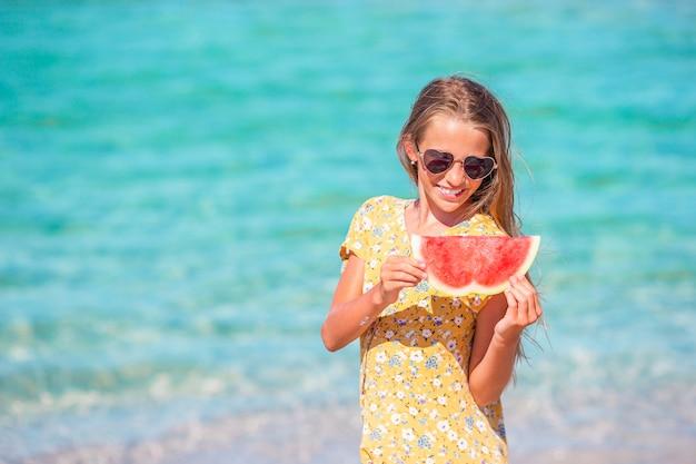 Criança feliz no mar com melancia