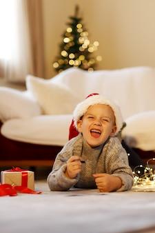 Criança feliz no natal escreva uma carta para o papai noel no chapéu de natal escrevendo a lista de desejos do presente próximo ao natal