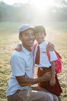 Criança feliz no primeiro dia de aula levada pelo pai pela manhã