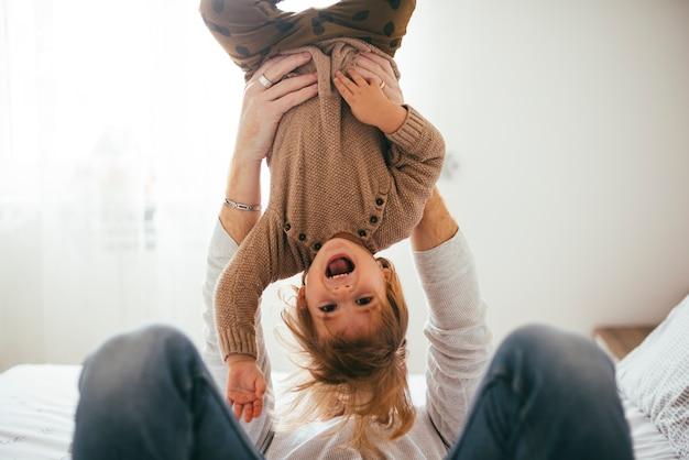 Criança feliz nos braços de cabeça para baixo