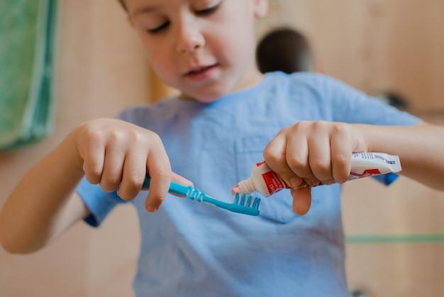 Criança feliz ou criança escovando os dentes no banheiro.