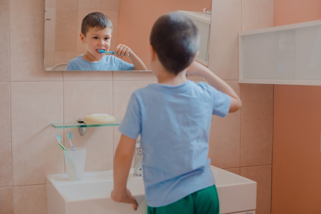 Criança feliz ou criança escovar os dentes no banheiro.
