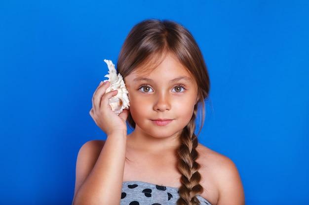 Criança feliz ouvir concha. férias de verão e o conceito de viagens