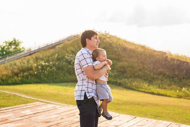 Criança feliz, pai e filho se divertindo, segurando as mãos em um pôr do sol