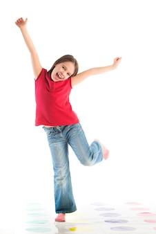 Criança feliz posando com roupas de criança, apoiada em uma perna só, com os braços levantados