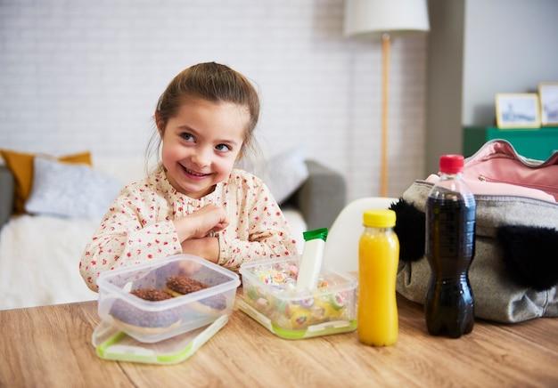 Criança feliz preparando lancheira com doces