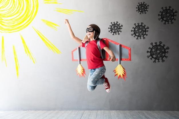 Criança feliz pulando com asas de papelão de brinquedo voando para longe do vírus cobiçoso.