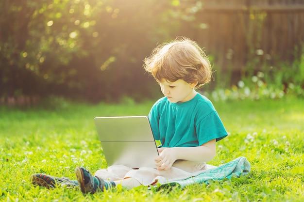 Criança feliz que joga o portátil que senta-se na grama verde no parque do verão.