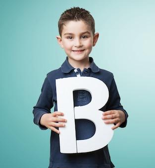 Criança feliz que prende a letra b