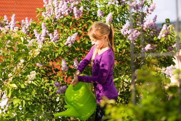 Criança feliz, regando flores no jardim