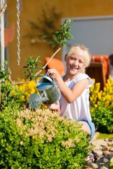 Criança feliz, regando flores
