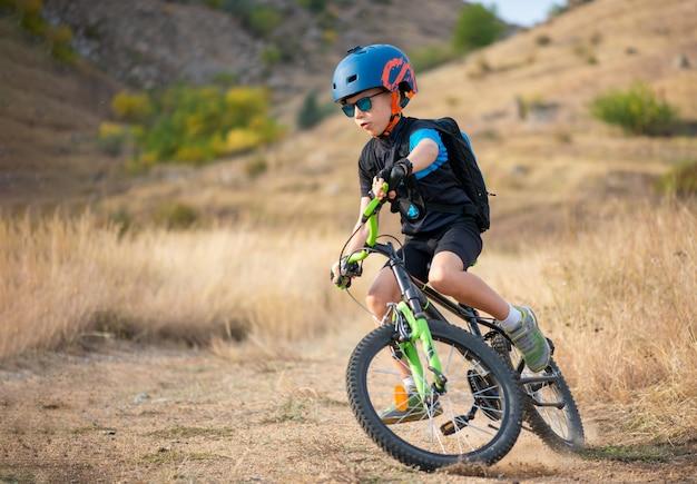 Criança feliz se divertindo no parque outono com uma bicicleta