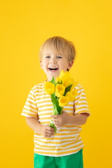 Criança feliz segurando buquê de tulipas primavera contra parede amarela.