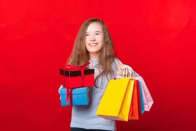 Criança feliz segurando duas caixas de presente e muitas sacolas coloridas e olhando para longe