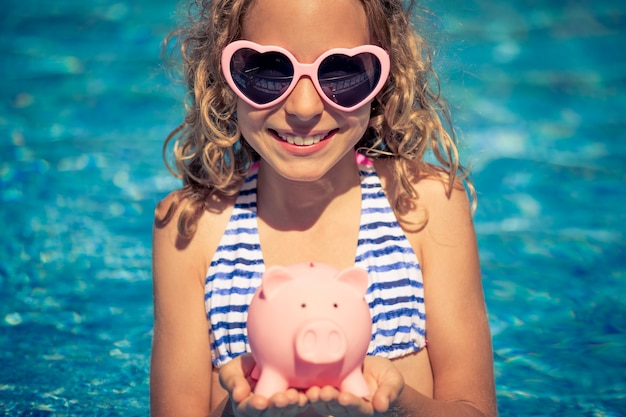 Criança feliz segurando o cofrinho contra a parede de água azul.