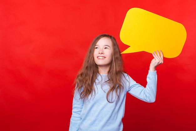 Criança feliz segurando um balão de fala amarelo e olhando para longe por cima da parede vermelha