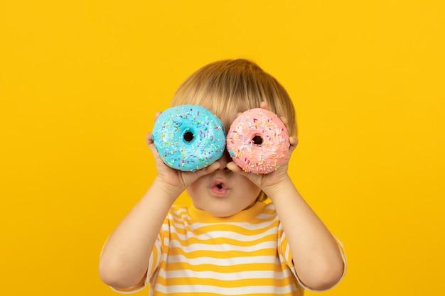 Criança feliz segurando um donut com cobertura