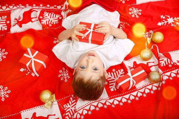 Criança feliz segurando um presente de natal. lindo menino loiro deitado no chão