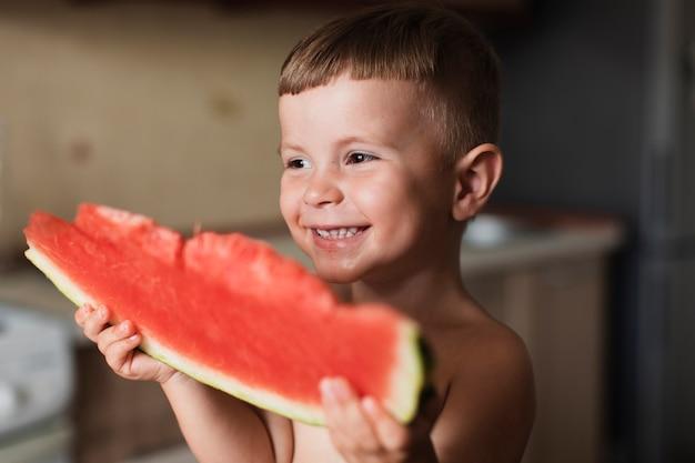 Criança feliz, segurando uma fatia de melancia