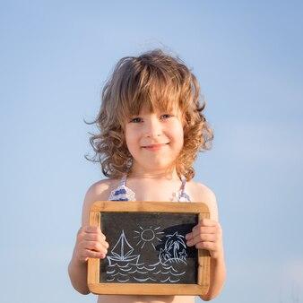 Criança feliz segurando uma lousa criança sorridente contra o céu azul