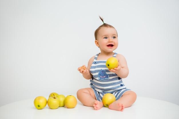 Criança feliz senta e come maçãs em um fundo branco